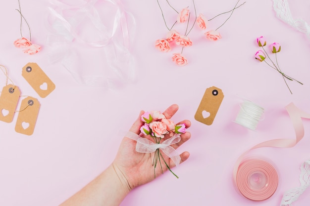Close-up of woman's hand holding flower tied with white ribbon against pink background Free Photo