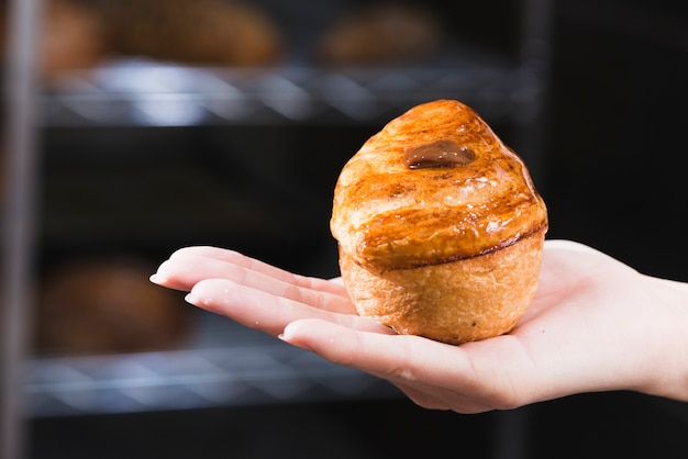 Close-up of woman's hand holding freshly baked sweet puff pastry Free Photo