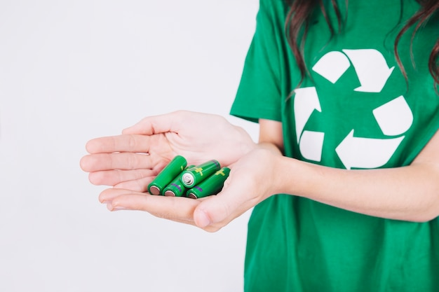 Close-up of a woman's hand holding green batteries Free Photo