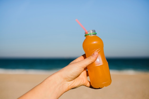 Close-up of woman's hand holding an orange juice plastic bottle with drinking straw at beach Free Photo
