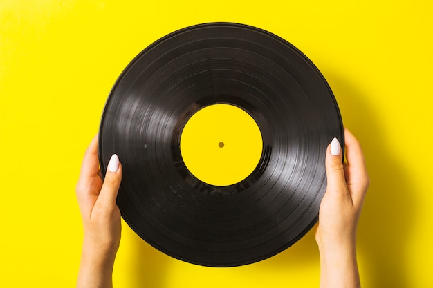 Close-up of woman's hand holding vinyl record on yellow background Free Photo