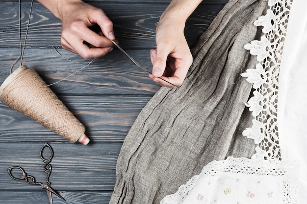 Close-up of woman's hand inserting string thread in needle with variety of textile Free Photo