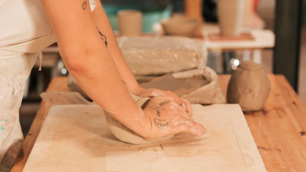 Close-up of woman's hand kneading clay on the board Free Photo