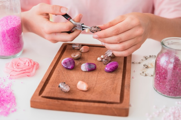 Close-up of woman's hand making the beads bracelet on wooden tray Free Photo
