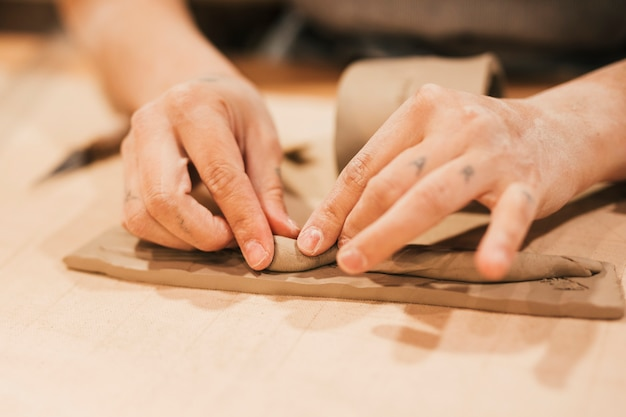Close-up of woman's hand molding the clay on wooden table Free Photo