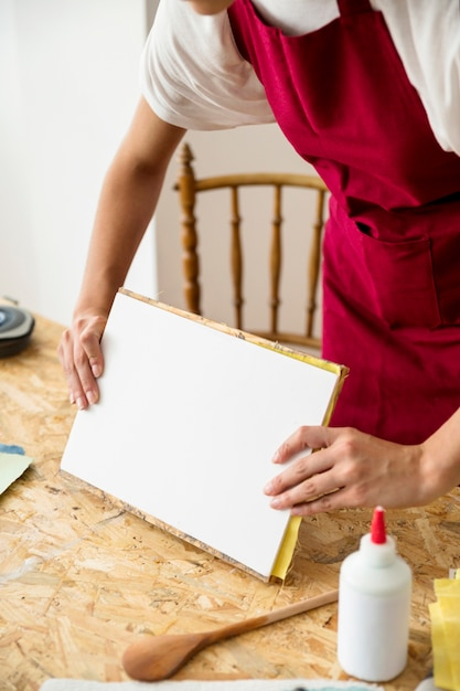 Close-up of a woman's hand preparing paper on wooden desk Free Photo