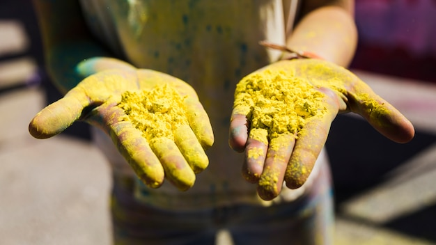 Close-up of woman's hand showing yellow holi color Free Photo