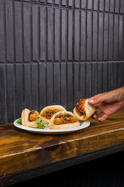 Close-up of woman's hand taking gua bao on white plate over the wooden table Free Photo