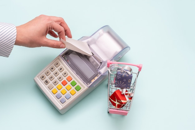 Close-up of a woman's hand tearing a check from an old cash register next to a cart with wrapped boxes of gifts Premium Photo