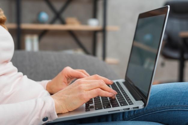 Primo piano della mano della donna che scrive sul computer portatile Foto Gratuite