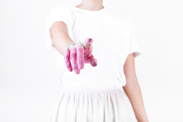 Close-up of a woman's hand with pink paint pointing finger Free Photo