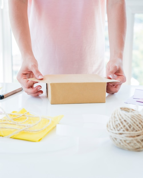 Close-up of a woman's hand wrapping the gift box on white table Free Photo