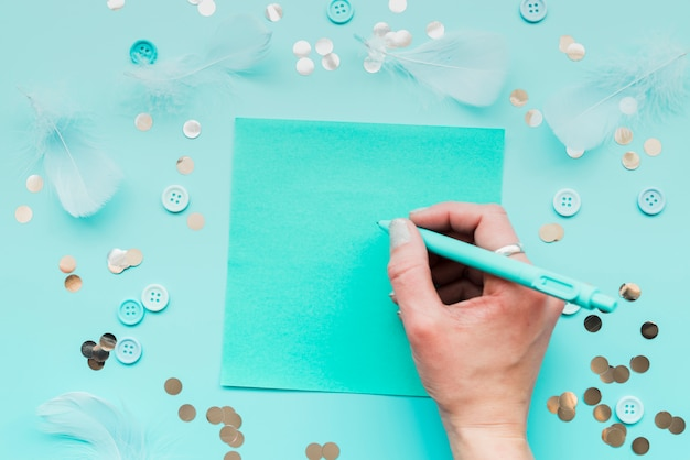 Close-up of woman's hand writing on paper with pen surrounded with feather; sequins and button on teal backdrop Free Photo