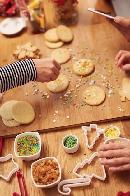 Chiuda in su delle mani della donna che decorano i biscotti per natale Foto Gratuite