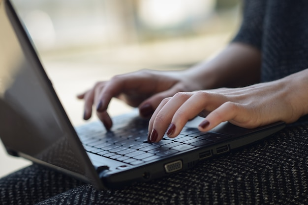 Close-up of woman's hands with painted nails typing on laptop Free Photo