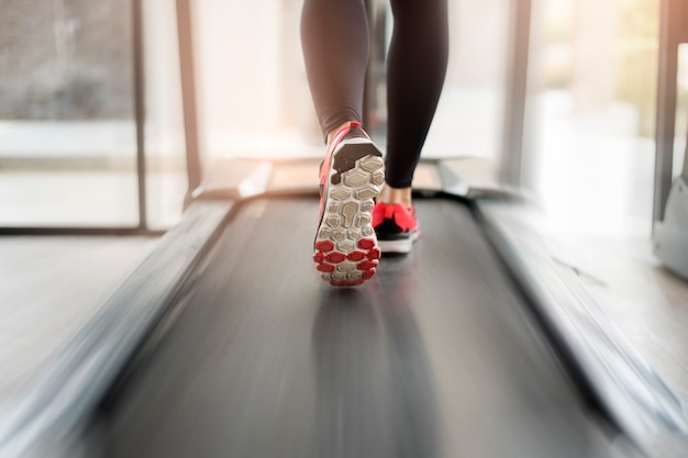 Close up of  woman's muscular legs feet running on treadmill workout at fitness gym Premium Photo