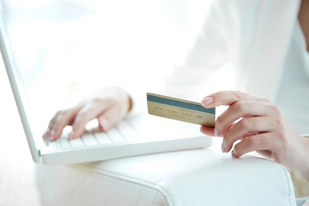 Close-up of woman shopping online with credit card and laptop Free Photo