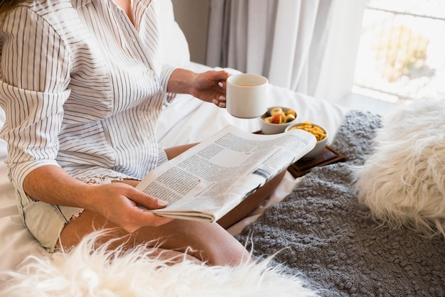 Close-up of a woman sitting on bed with newspaper and coffee cup in hand Free Photo