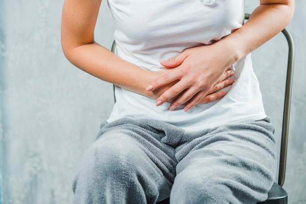 Close-up of a woman sitting on chair having stomach ache Free Photo