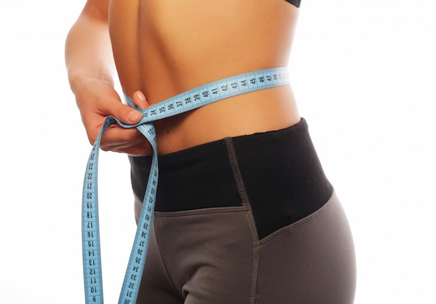 Close up of a woman in sportswear measuring her waist Premium Photo