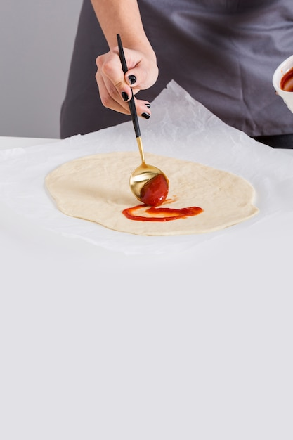 Close-up of a woman spreading the tomato sauce on pizza bread over the parchment paper Free Photo