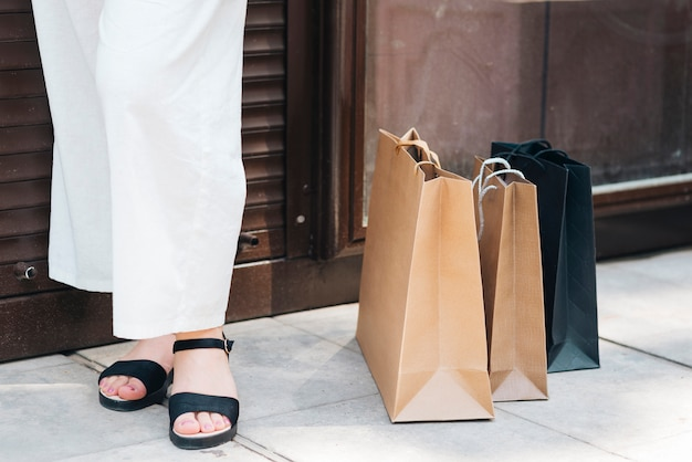 Close-up woman standing near shopping bags Free Photo
