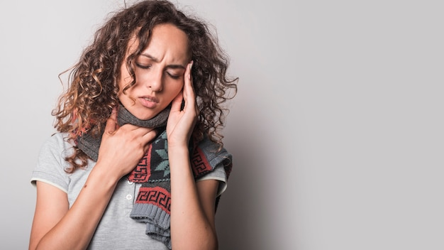 Close-up of woman suffering from flu having headache against gray background Free Photo