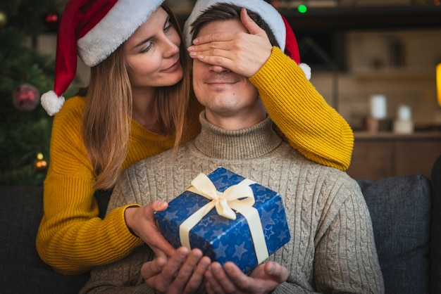 Close up woman surprising man with gift Free Photo