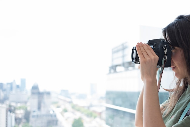 Close-up of a woman taking pictures on dslr camera Free Photo