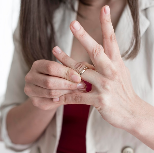 Close-up woman taking wedding ring off finger Free Photo