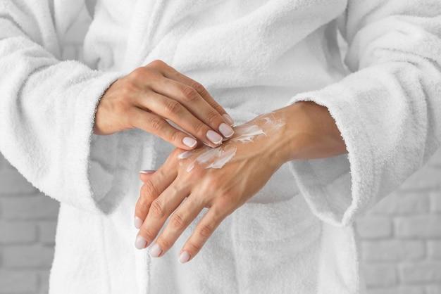 Donna del primo piano che prova le mani crema Foto Gratuite