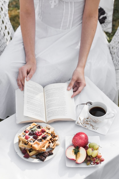 Close-up of a woman turning pages of book with breakfast and coffee on table Free Photo