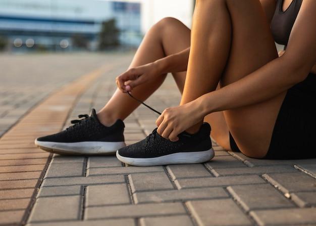 Женщина крупным планом, завязывающая шнурки Бесплатные Фотографии