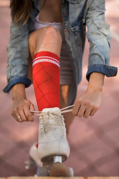 Close-up of a woman tying the lace of roller skater Free Photo