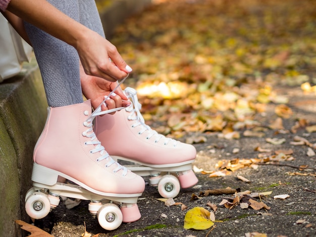 Close-up of woman tying shoelaces on roller skates Free Photo
