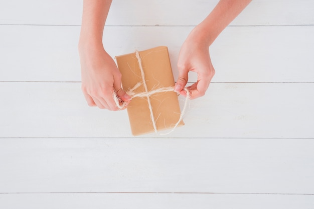 Close-up of a woman tying the thread on brown wrapped gift box on wooden desk Free Photo
