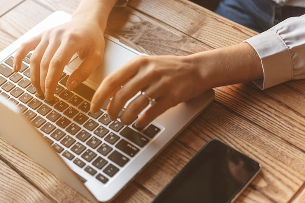 Close up of woman typing on laptop in coffee shop Premium Photo