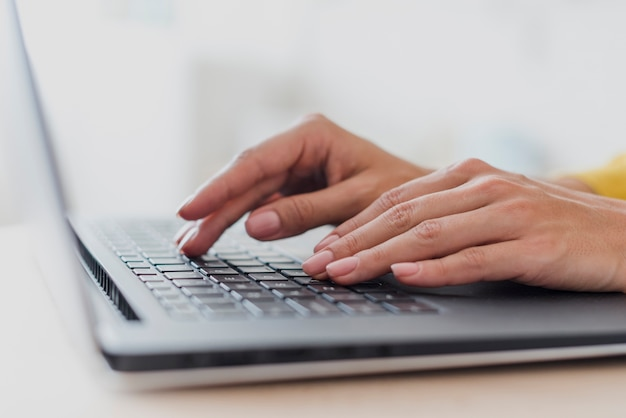 Close-up woman typing on laptop's keyboard Free Photo