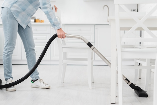 Close-up woman using vacuum to clean Free Photo