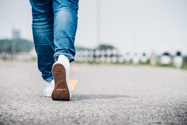 Close up woman wear jean and white sneaker walking forward on highway road in sunny day Premium Photo