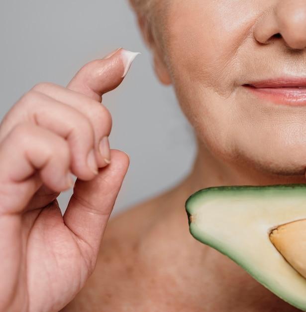 Donna del primo piano con avocado e crema Foto Gratuite