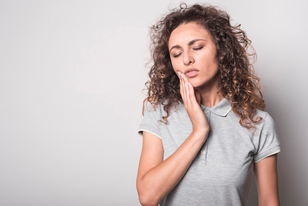 Close-up of woman with curly hair suffering from toothache over gray background Free Photo