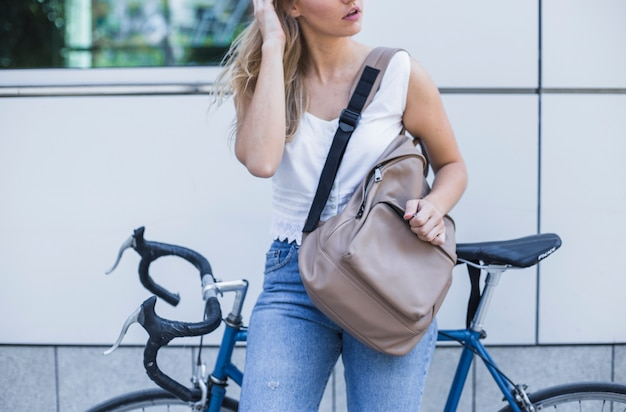Close-up of woman with her backpack leaning on bicycle Free Photo