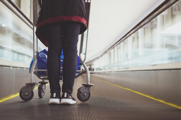Close up woman with luggage trolley in airport escalator Premium Photo