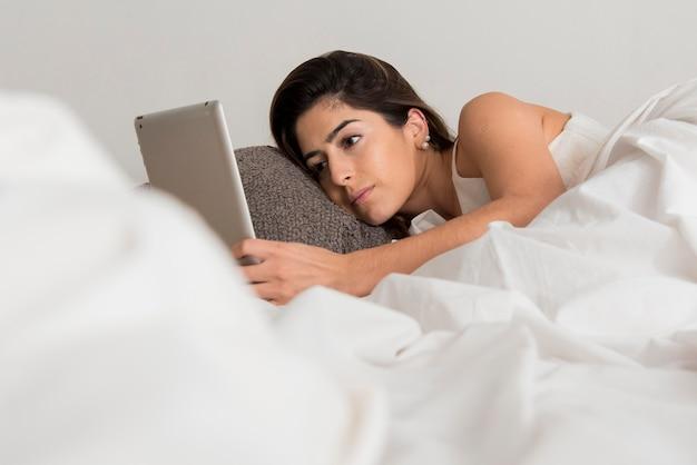 ベッドの中でタブレットを持つクローズアップ女性 無料写真