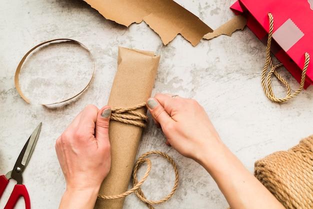Primo piano della donna che avvolge il contenitore di regalo con corda di iuta sul contesto strutturato Foto Gratuite