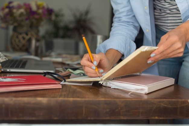 Close-up of woman writing on notebook Free Photo