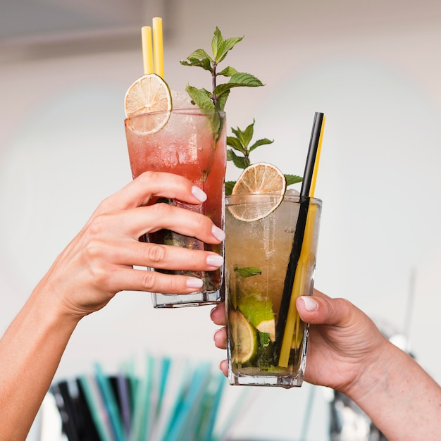 Close-up women enjoying cocktail glasses Free Photo