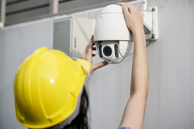 Close up of women technician fixing cctv camera on wall Premium Photo