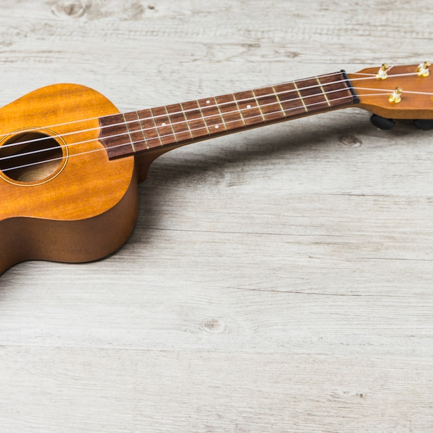 Close-up of wooden acoustic guitar on table Free Photo